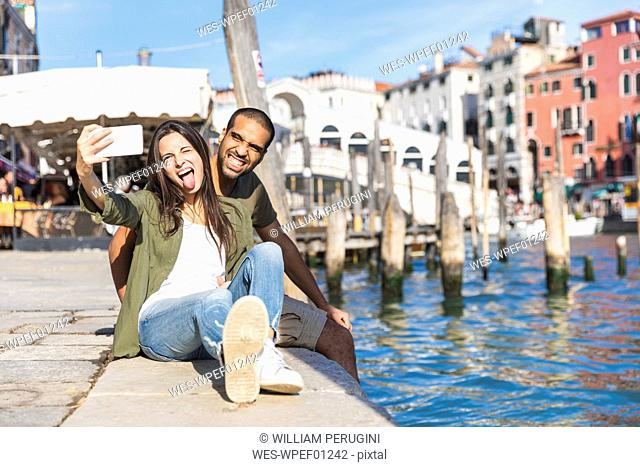 Italy, Venice, playful couple relaxing and taking a selfie with Rialto bridge in background