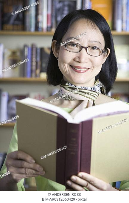 Middle-aged Asian woman reading book