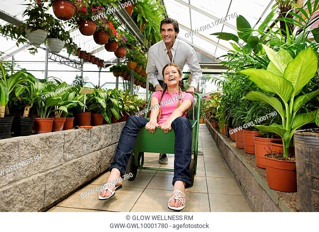 Man pushing a woman sitting on a push cart in a greenhouse