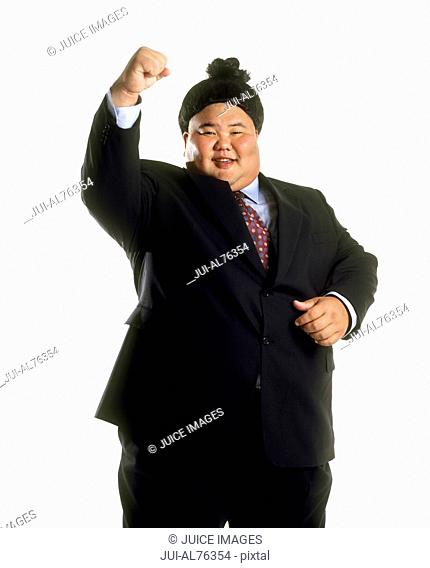Portrait of a sumo wrestler in a business suit celebrating