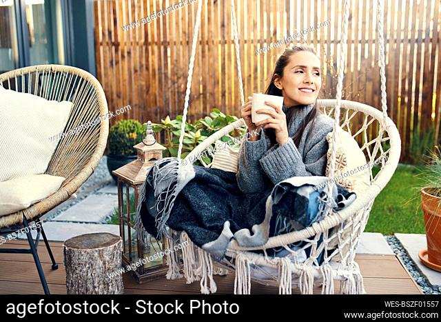 Smiling young woman holding mug while relaxing on swing in garden