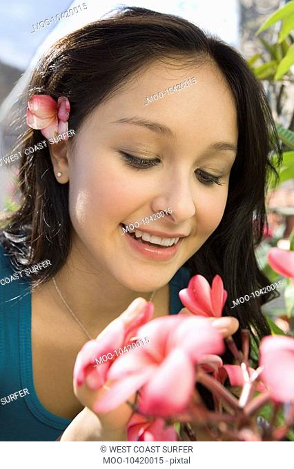 Young woman smelling exotic plat in greenhouse close-up