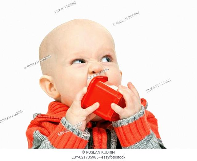 little boy chewing on a plastic pyramid in the studio
