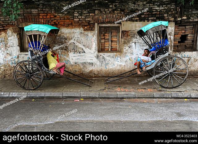 Kolkata (Calcutta), West Bengal, India, Asia - Two rickshaw pullers rest on their traditional old style wooden rickshaws at the roadside in the Indian...