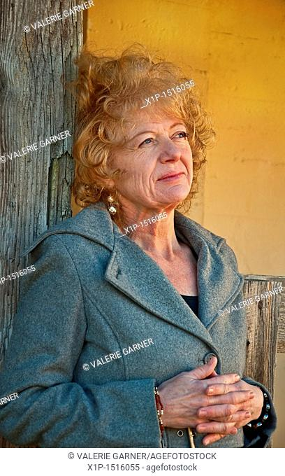 This Caucasian woman is in a thoughtful pose, wearing professional clothing in a rustic setting  She has strawberry blond hair and is in her fifties  Vertical...