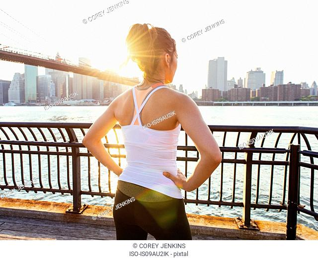 Young female runner looking at East River, New York, USA