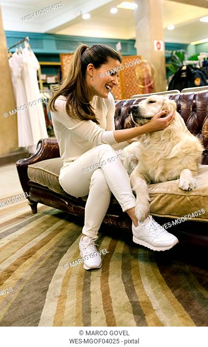 Happy woman with dog sitting on couch in a vintage shop