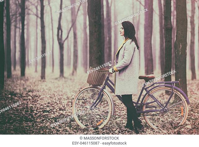 portrait of a young woman with a bicycle and suitcase standing in the middle of the forest