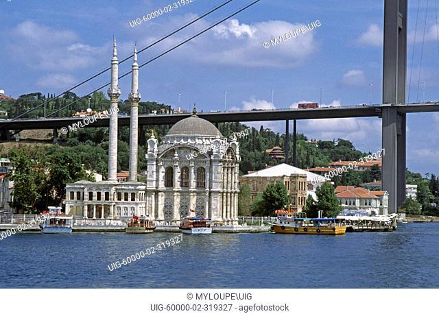 THE ORTAKOY MOSQUE sits underneath the BOGAZICI KORPUSU bridge on the BOSPHORUS - ISTANBUL, TURKEY