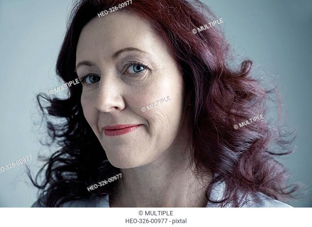 Portrait confident Caucasian mature woman with curly burgundy red hair