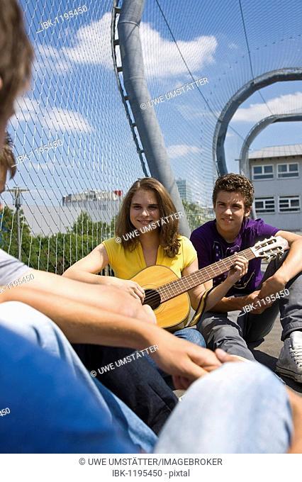 Girl playing the guitar, three boys listening