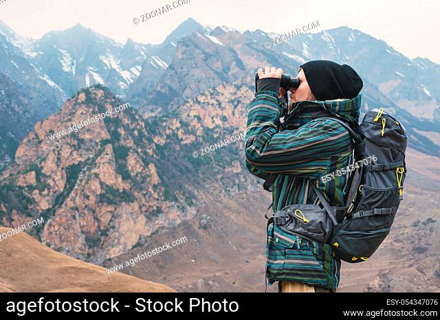 A hipster man with a beard in a hat, jacket, and a backpack in the caucasian mountains holds binoculars in his hands and looks into the distance, adventure