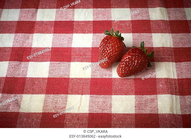fresh red strawberries in a red bowl on checkered tablecloth