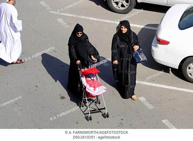 MUSCAT, OMAN Muttrah old town district with corniche and souk. Young mother wearing a burqa
