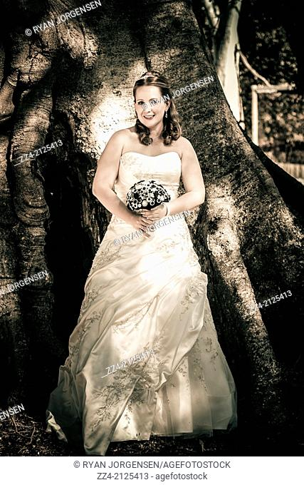 Full length outdoor portrait of a beautiful young bride in late twenties to early thirties standing next to big tree trunk during outback country wedding in...