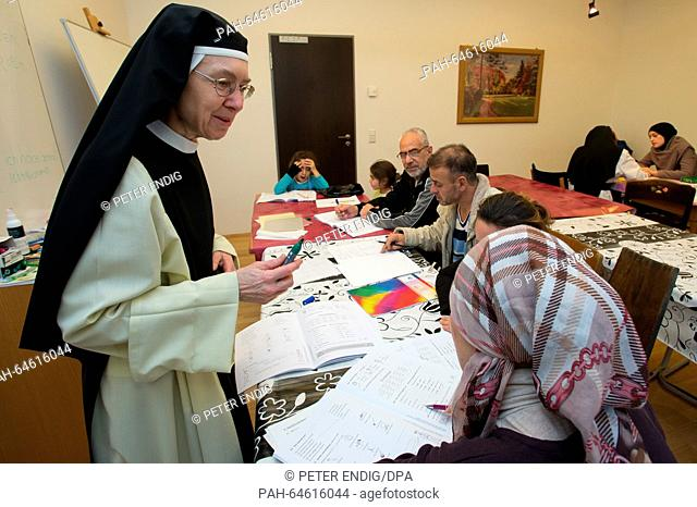 Sister Katharina Gutlederer (L) assists Syrian refugess during a German language course in the Cistercienserinnen Monastery St