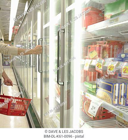 Man opening freezer door at supermarket, Perth, Australia