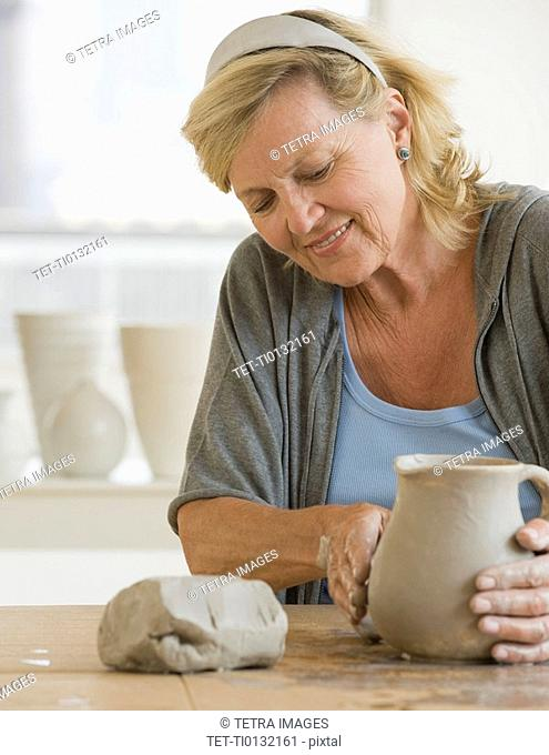 Senior woman making ceramic pot