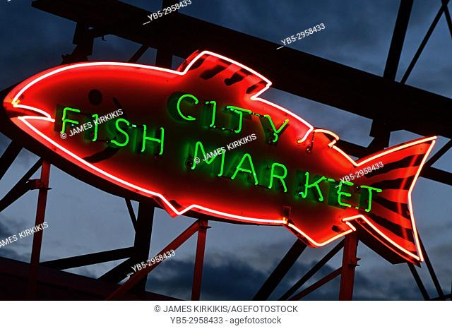 A neon fish hangs on a sign of the renown Pike Market in Seattle