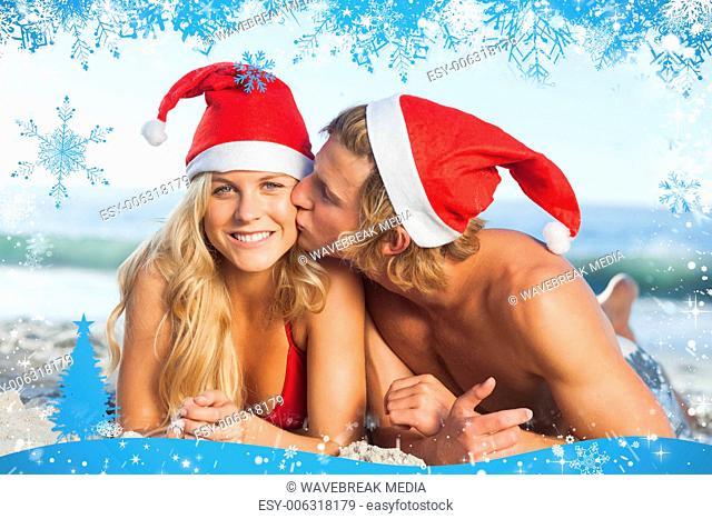 Man giving kiss to partner wearing christmas hats
