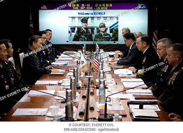 US Admiral Mike Mullen center right sits across the table from his South Korean counterpart center left to discuss transferring wartime operational control of...
