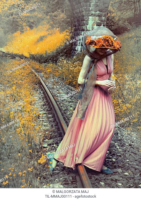 A woman in a pink flowing dress, blue shoes and a red flowery hat, holding a little yellow flower & crossing a railway on a sunny day