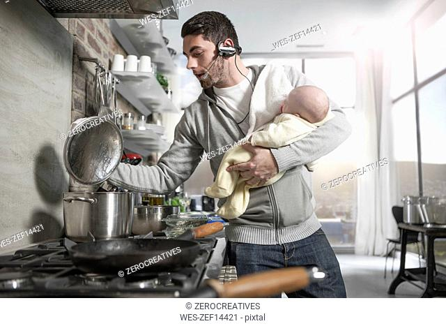 Father with headset cooking in kitchen holding baby