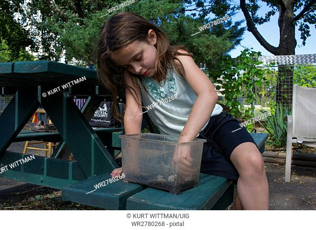 Girl Playing with Bugs in Garden