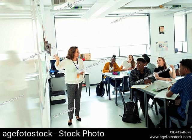 High school students watching teacher leading lesson at whiteboard in classroom