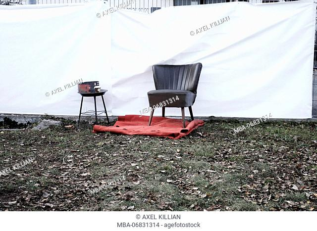 Old black armchair on red carpet and barbecue in front of fence with white plastic sheet