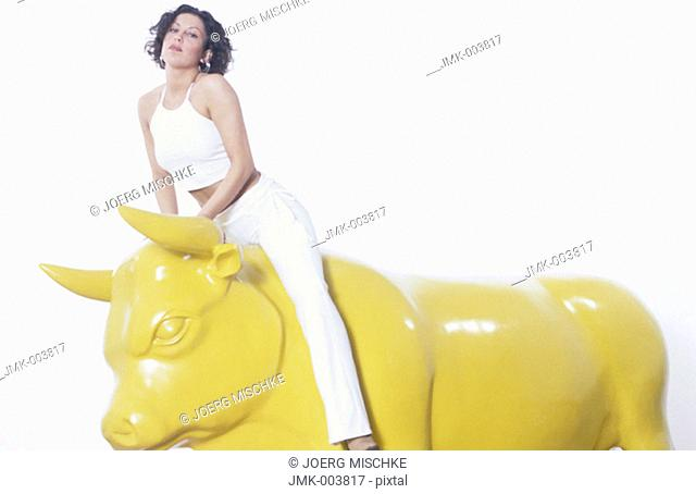 Studio picture of a young woman, 15-20 20-25 25-30 years old, sitting on a yellow bull, wearing white pants and a white shirt