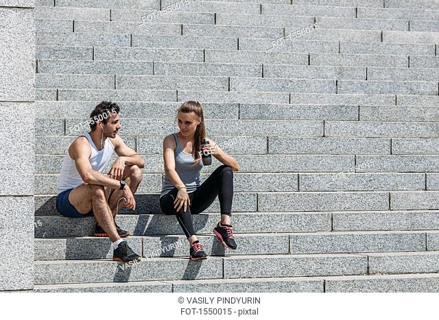 Friends talking while sitting on steps after exercising