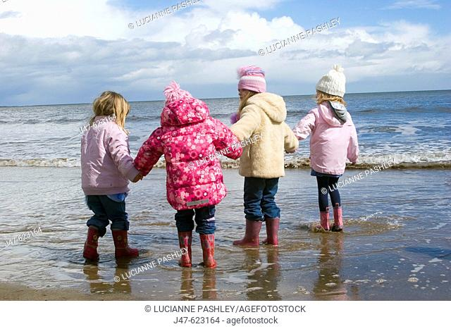 Group of 4, 4 year old girls standing on the seashore all in a row holding hands, dressed in winter clothing