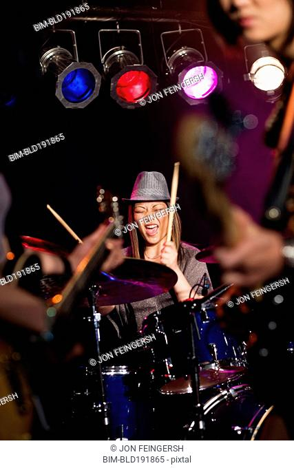 Asian woman playing drums onstage