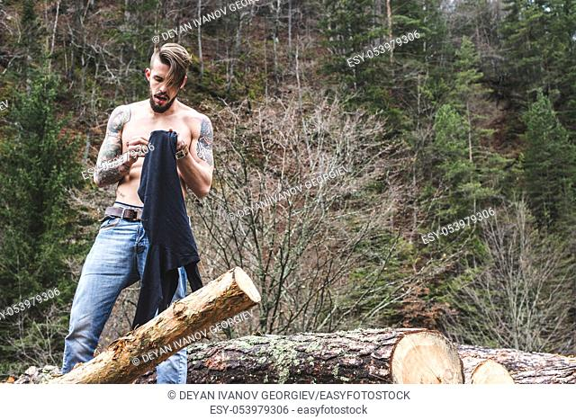 Young men on logs in the forest. Men dress