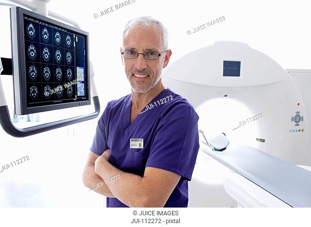Portrait smiling doctor reviewing digital brain scan at CT scanner in hospital