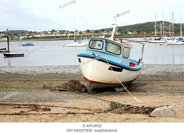 A old wood boat park alone on the sand at the beach