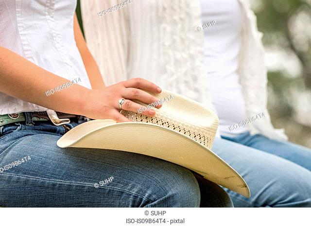 Mid section of two women sitting holding cowboy hat on ranch, Bridger, Montana, USA