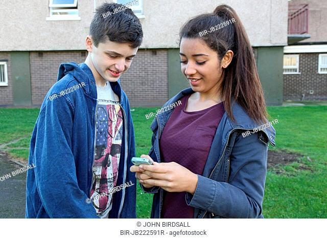 Teenage girl and boy looking at mobile phone