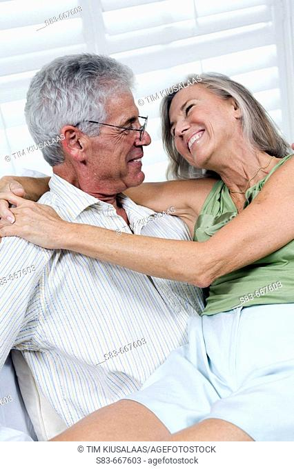 Senior couple being romantic. Woman sitting on mans lap