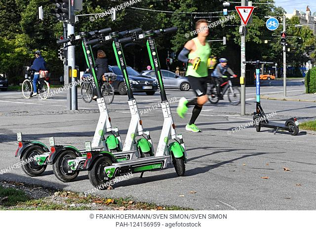 Three electric scooters are arranged side by side - in the background a jogger jogs past, run, runners, pedestrians. LimeBike
