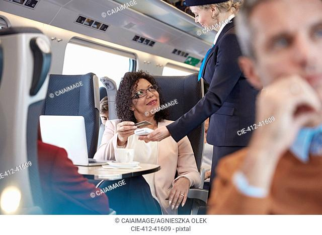 Woman with credit card using contactless payment, paying attendant on passenger train