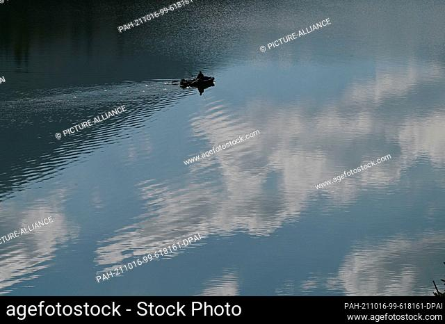 16 October 2021, Bavaria, Lenggries: An angler sails across the Sylvenstein reservoir in his rowing boat. The surrounding mountains