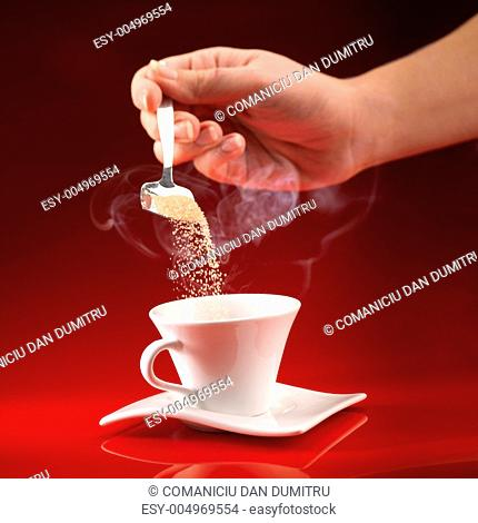 hand pouring sugar in coffee cup