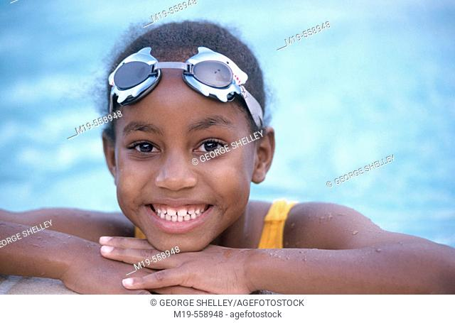 girl poolside in swim goggles