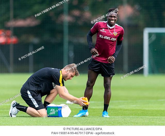 14 August 2019, Saxony, Dresden: Soccer: 2nd Bundesliga, Training, SG Dynamo Dresden. Dynamo's physiotherapist Julian Binder (l) provides Moussa Kone with care...