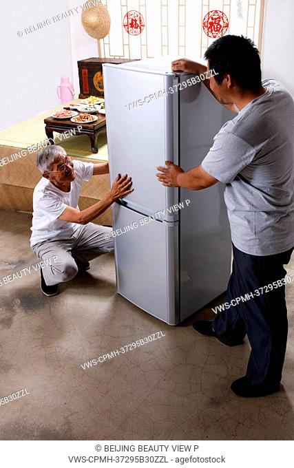 Two men standing by refrigerator