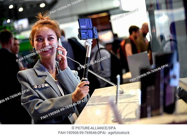 06 September 2019, Berlin: A young woman tries out various smartphones at the IFA technology fair, the world's largest trade fair for entertainment and consumer...