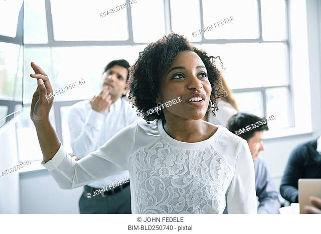 Businesswoman talking near visual screen in meeting