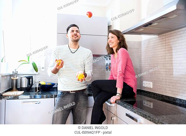 Young man juggling apples for girlfriend in kitchen